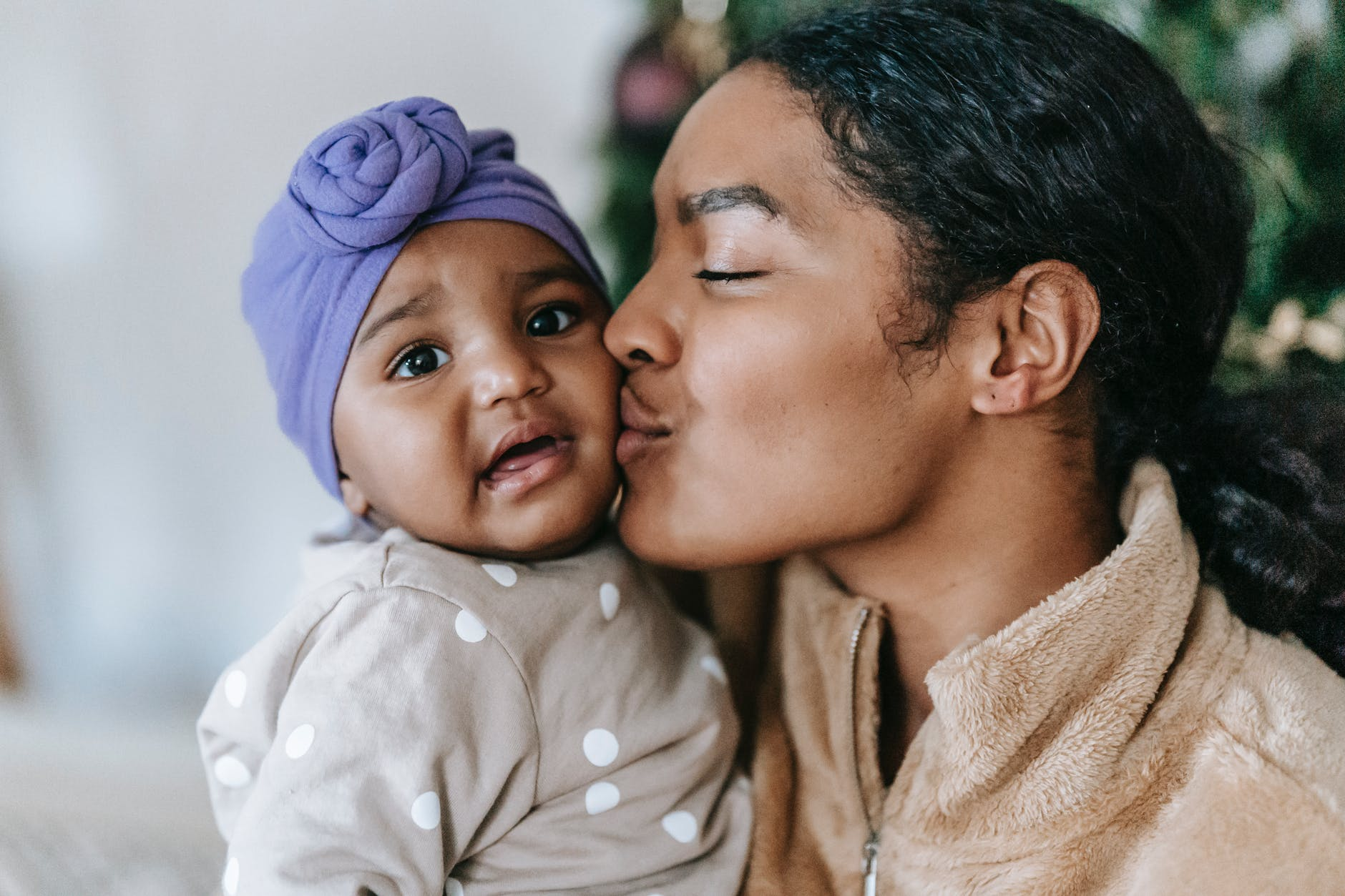 loving black mother kissing little daughter with mouth opened
