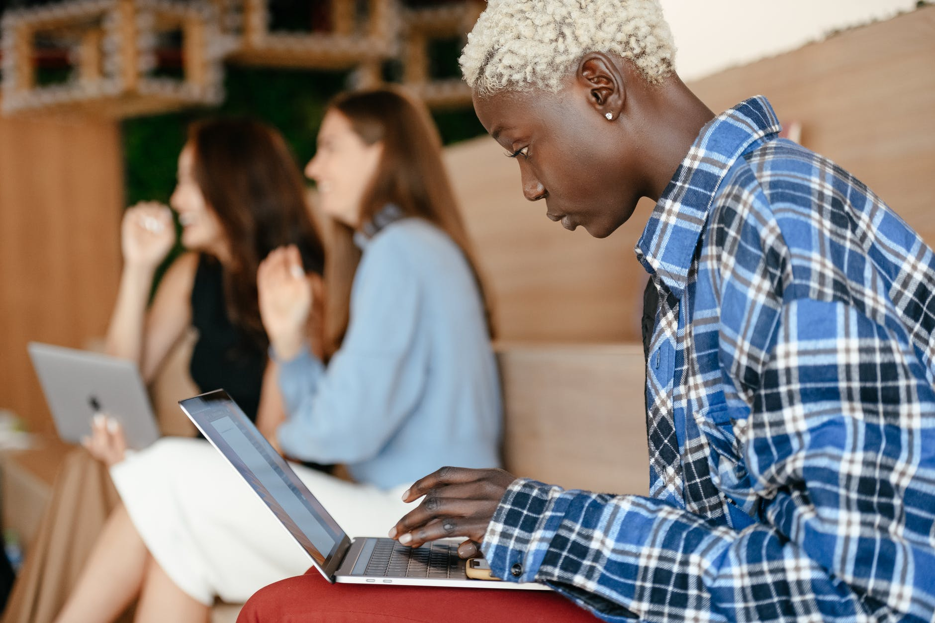 serious black woman typing on laptop among diverse colleagues