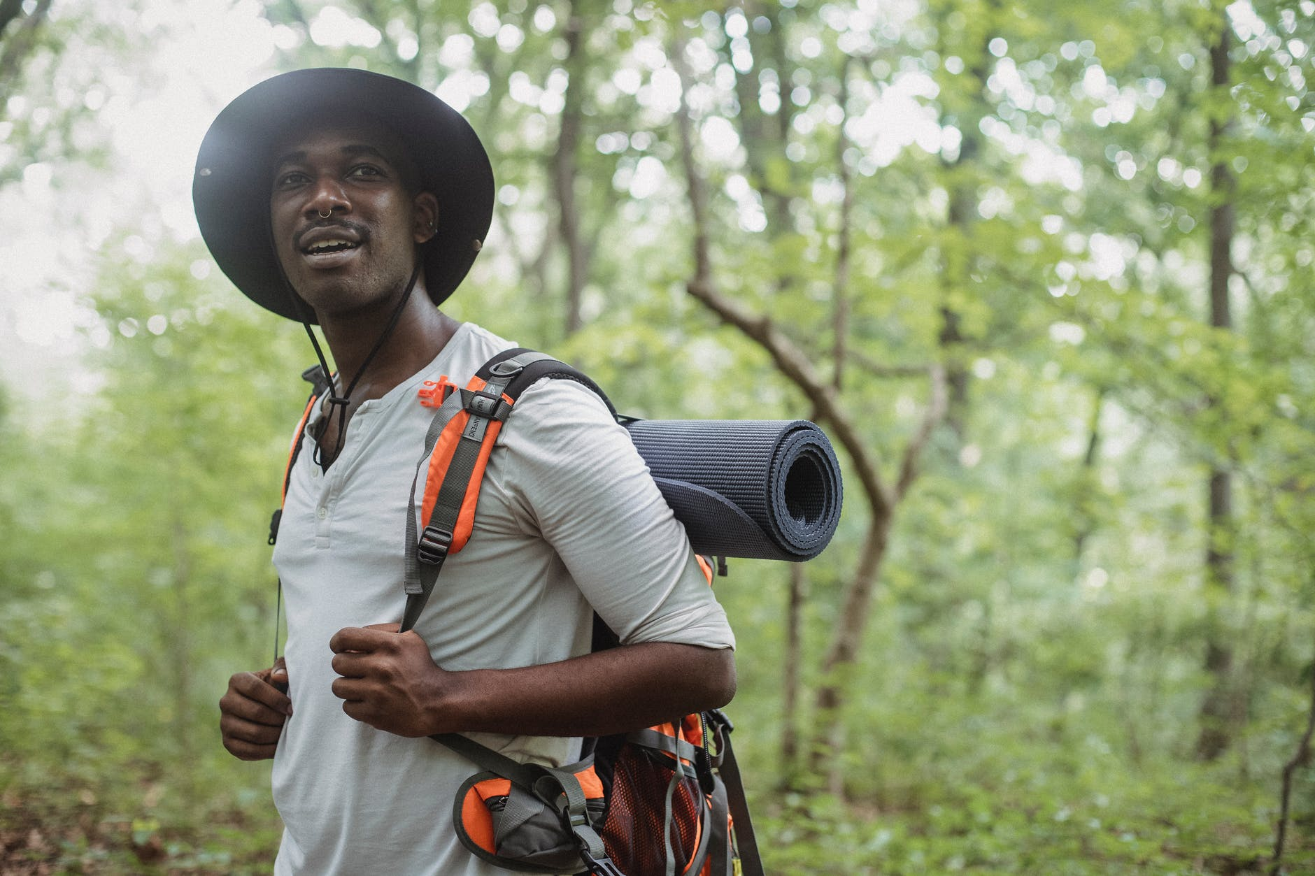 positive black man standing with trekking backpack in forest