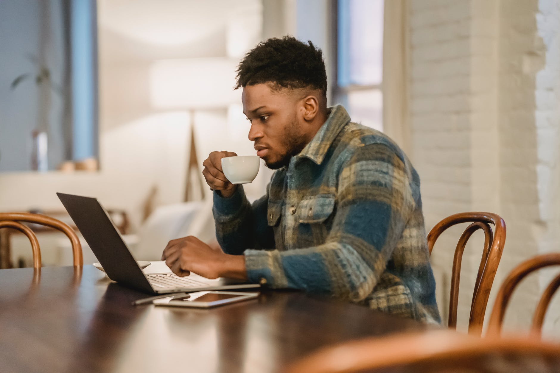 concentrated black man working on laptop and drinking coffee